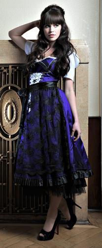 Anina W: dunkel-lila Seidendirndl mit schwarzer Spitzenschürze, Trachtenhäkchen, Charivari mit Strass, Svarovskisteine, inkl. Bluse mit gefälteltem Ausschnitt, ca. € 1050,-